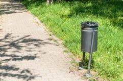Nuevo cubo de la basura del metal en el parque en la ciudad con el bolso plástico negro de los desperdicios para recoger la liter Foto de archivo libre de regalías