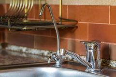 Nuevo grifo de agua brillante del metal en cocina moderna Imagen de archivo libre de regalías