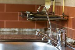 Nuevo grifo de agua brillante del metal en cocina moderna Fotos de archivo libres de regalías