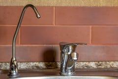 Nuevo grifo de agua brillante del metal en cocina moderna Imagenes de archivo