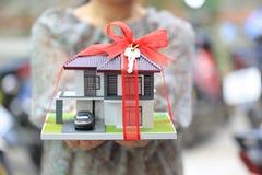 Nuevo hogar del regalo y concepto de las propiedades inmobiliarias, el sostenerse femenino de las manos del hombre fotografía de archivo libre de regalías
