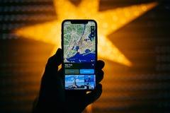 Nuevo iPhone de Apple contra la estrella defocused azul que ofrece GPS nuevo Fotos de archivo libres de regalías