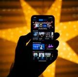 Nuevo iPhone de Apple contra la estrella defocused azul que ofrece las películas s Foto de archivo libre de regalías