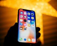 Nuevo iPhone de Apple contra la estrella defocused azul que ofrece los apps caseros Foto de archivo libre de regalías