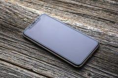 Nuevo iPhone X 10 en un fondo de madera, tiro del estudio Foto de archivo
