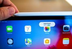 Nuevo lápiz de Apple que carga en la favorable tableta del iPad imagenes de archivo