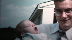 1958 - Nuevo papá que detiene al bebé contra el abuelo que detiene al bebé almacen de video