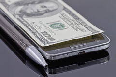Nuevo smartphone, bolígrafo y cientos dólares Foto de archivo