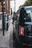 Nuevo taxi eléctrico del negro de LEVC TX Londres que carga de punto de cambio en Londres, Reino Unido fotografía de archivo libre de regalías