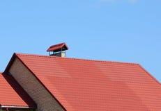 Nuevo tejado tejado rojo con exterior de la construcción de la techumbre de la casa de la chimenea del metal Construcción de la t Fotos de archivo