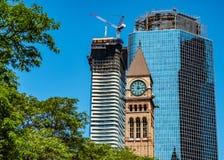Nuevo underconstruction de los rascacielos que empequeñece la torre de reloj vieja fotos de archivo libres de regalías