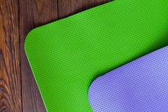 Nuevo yogamat verde y púrpura en un fondo de madera Fotos de archivo