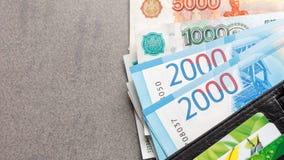 Nuevos billetes de banco rusos en denominaciones de 1000, 2000 y 5000 rublos y tarjetas de crédito en un primer de cuero negro de Imagenes de archivo
