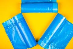 Nuevos bolsos de basura azules en un fondo amarillo Foto de archivo