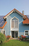 Nuevos casa y jardín construidos modernos, tejado con las células solares Foto de archivo libre de regalías