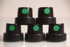 Nuevos casquillos de la pintura del aerosol de las latas para la pintada que se coloca en la forma de un fondo del blanco del pri Foto de archivo libre de regalías