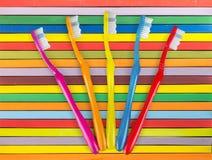 Nuevos cepillos de dientes coloridos en fondo rayado Imagen de archivo