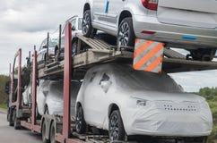 Nuevos coches para la venta en la plataforma del camión Imágenes de archivo libres de regalías