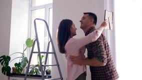 Nuevos dueños caseros, abrazo masculino feliz y mujer que circunda en brazos durante mejoras para el hogar en el apartamento almacen de metraje de vídeo