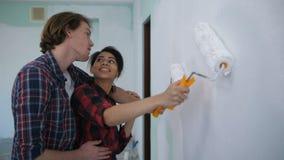 Nuevos dueños de la casa felices en pared de la pintura del abrazo del amor metrajes