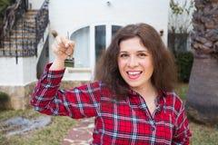 Nuevos hogar, casa, propiedad y arrendatario - mujer divertida joven que se sostiene dominante delante de su nuevo hogar después  fotos de archivo libres de regalías