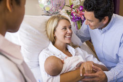 Nuevos padres con el bebé que habla con el doctor Imágenes de archivo libres de regalías