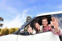 Nuevos pares felices automotrices que muestran llaves del coche Foto de archivo libre de regalías