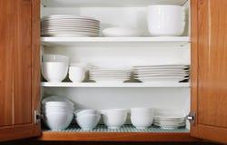 Nuevos platos y tazones de fuente blancos en cabina de cocina imagen de archivo