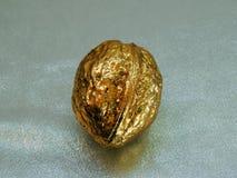 Nuez de oro hecha de la hoja de oro en un fondo plateado Imagenes de archivo