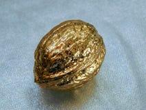 Nuez de oro hecha de la hoja de oro en un fondo plateado Imagen de archivo