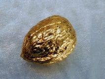 Nuez de oro hecha de la hoja de oro en un fondo plateado Imagen de archivo libre de regalías