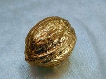 Nuez de oro hecha de la hoja de oro en un fondo plateado Foto de archivo