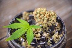Nug e smerigliatrice della cannabis sopra fondo di legno fotografie stock libere da diritti