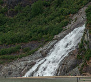 Nugget Falls. Juneau, AK, USA - May 25, 2016: Visitors watch the majesty of Nugget Falls located adjacent to the Mendenhall Glacier royalty free stock photography
