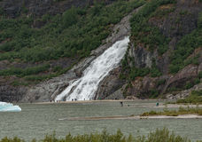 Nugget Falls. Juneau, AK, USA - May 25, 2016: Visitors watch the majesty of Nugget Falls located adjacent to the Mendenhall Glacier royalty free stock photo