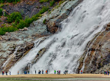 Nugget Falls Visitors. Juneau, AK, USA - May 25, 2016: Visitors watch the majesty of Nugget Falls located adjacent to the Mendenhall Glacier stock photography