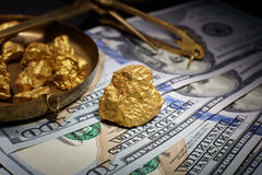 Nugget gold and dollar bills royalty free stock photo