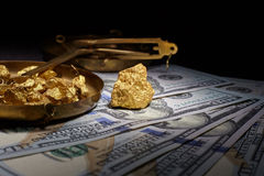 Nugget gold and dollar bills stock images