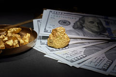 Nugget gold and dollar bills stock photo