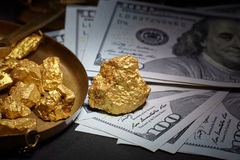 Nugget gold and dollar bills stock photography