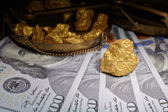 Nugget gold and dollar bills stock image