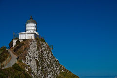 Nugget Point Lighthouse - New Zealand. Lighthouse with bright blue sky. Nugget Point Lighthouse, New Zealand Royalty Free Stock Photos