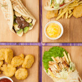 Nuggets and french fries, shawarma, Greek gyros and pita with chocolate and kiwi on boards on a table. French fries and nuggets, Arabic shawarma, Greek gyro and Royalty Free Stock Image