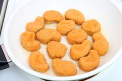 Nuggets. Some fresh nuggets of chicken meat in a pan Stock Image