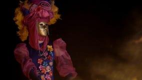Nuit foncée une fille mystérieuse dans un masque et une danse colorée de costume dans un feu brûlant banque de vidéos