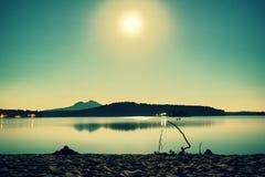Nuit romantique de pleine lune au lac, le niveau d'eau calme avec la lune rayonne Burh sur la colline Image stock