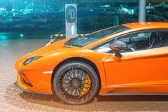 Nuit superbe orange d'e-voiture sur les rues réapprovisionnant en combustible pour l'e-mobilité de voitures électriques Image stock