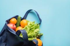 Nul afvalconcept Blauwe het winkelen katoenen textielzak met verse sinaasappel en groenten Ruimte voor tekst royalty-vrije stock fotografie