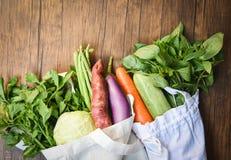 Nul plastic concept van het afvalgebruik minder/Verse groenten organisch in eco katoenen stoffenzakken op houten lijst stock foto