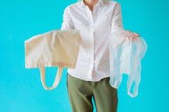 Null überschüssiges Konzept Frau, die zwischen Textilmultigebrauchstasche und Plastik wählt lizenzfreie stockfotos